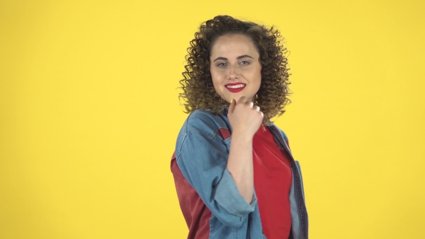 Lovely girl coquettishly smiling, waving hand and showing gesture come here on yellow background at studio, slow motion. Girl with curly hair in a denim suit with shorts and a red T-shirt | Shutterstock HD Video #1036171949