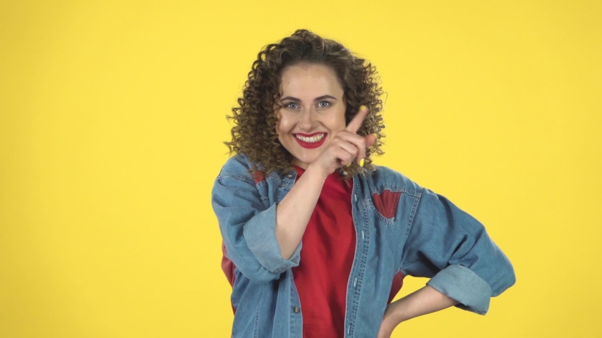 Girl thinks and listens, looking into the camera with a fork forward, shows the index finger straight against yellow background at studio, slow motion. Girl with curly hair in a denim suit and a red T | Shutterstock HD Video #1036171961
