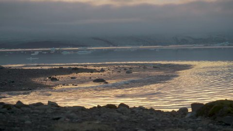 Gentle waves rolling onto a rocky beach with melting icebergs in the distance.