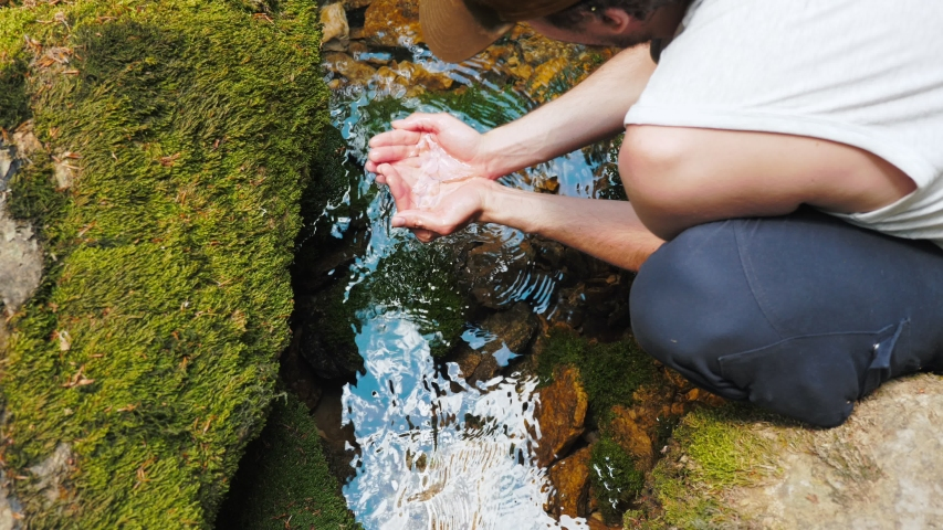 A young traveler man drinks clean clear water from a mountain river or spring. A man scooped up cold transparent water with his hands. | Shutterstock HD Video #1036195823