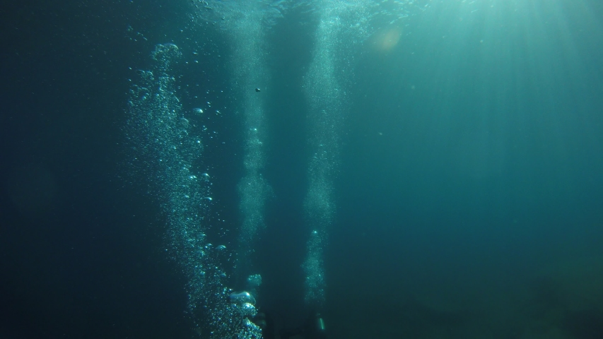 SCUBA divers swim towards a deep a ship wreck in very dark blue water.  Their bubbles are the only thing well illuminated from the distant sun. #1036207484