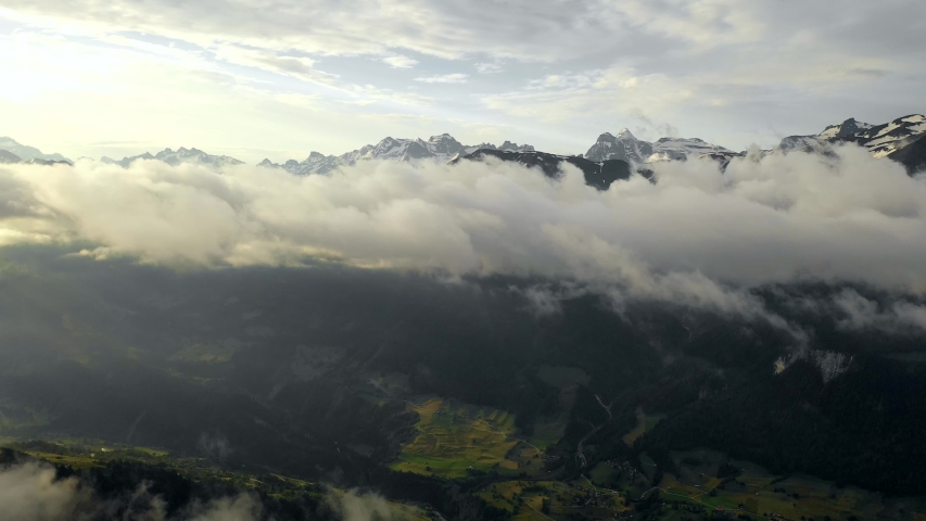 Aerial, drone shot, over forest and a valley, towards clouds and snowy mountains, at sunrise, on a sunny, summer morning, in Wallis, Switzerland   Shutterstock HD Video #1036207811