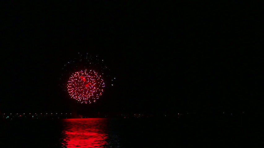 The fire scattering of fireworks in the night sky above the river is reflected in the water. Time laps | Shutterstock HD Video #1036222379