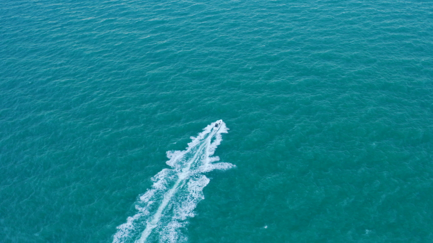 Sport fishing boat crashing through waves in open sea leaving trail of whitecap, tracking aerial view | Shutterstock HD Video #1036226963
