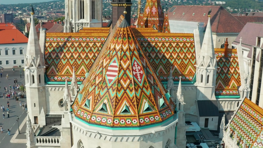 Budapest, Hungary - 4K drone flying away from the beautiful roof of Matthias Church in front of the Fisherman's Bastion at the heart of Buda's Castle District on a bright summer day | Shutterstock HD Video #1036227377