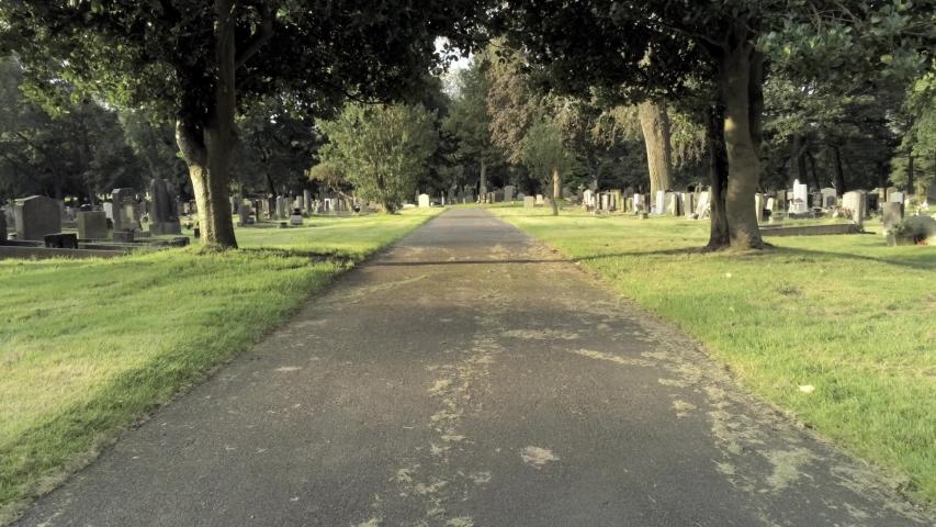 Cemetery aerial along pathway under trees tilting upwards passing gravestones.