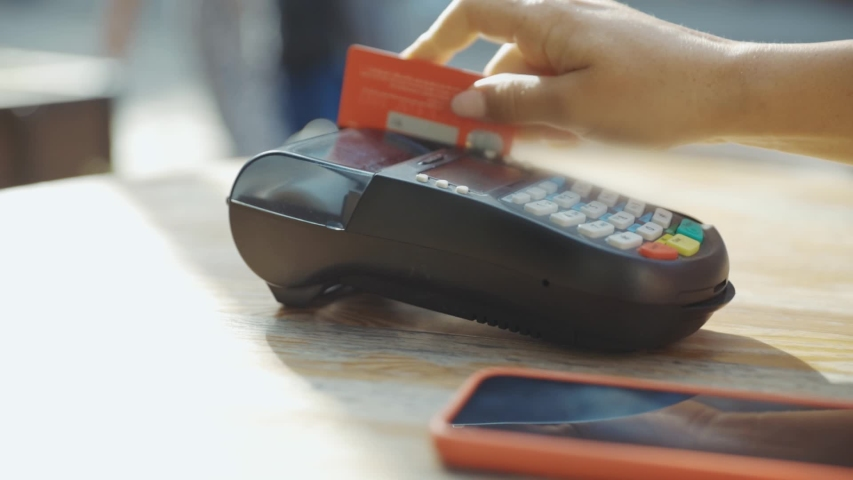 Young woman swiping debit card on cash machine in outdoor cafe close-up. Female hand with credit card using pos terminal for easy transaction. Royalty-Free Stock Footage #1036241039