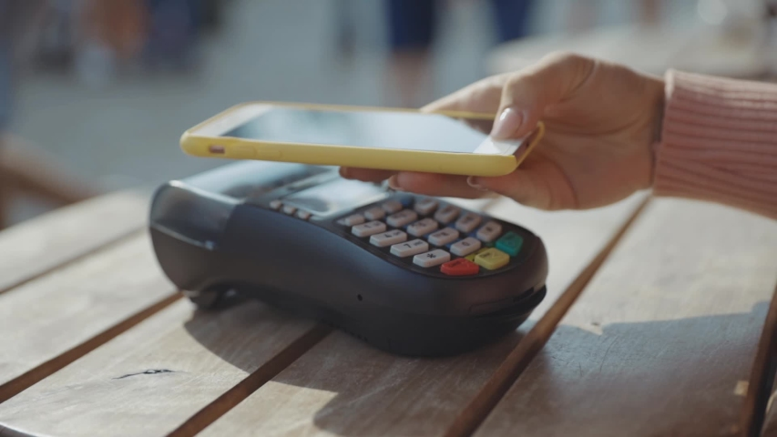 NFC fast payment. Close-up of female customer in the cafe using mobile phone making online contactless payment with NFC technology. Royalty-Free Stock Footage #1036241189
