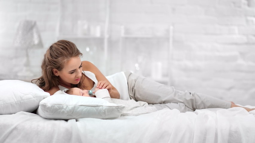 Lovely smiling mother lying on comfortable white bed lulling cute baby having positive emotion