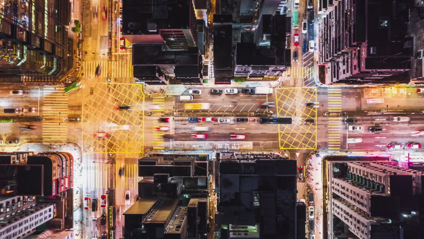 4K UHD Time-lapse of car traffic on road and people crossing street at night in Hong Kong downtown district, drone aerial top view. Commuter, Asia city life, or public transportation concept, Zoom out Royalty-Free Stock Footage #1036252025