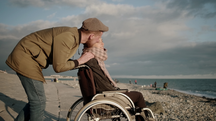 Loving couple enjoying the time together. Careful man and his disabled girlfriend in wheelchair by the sea