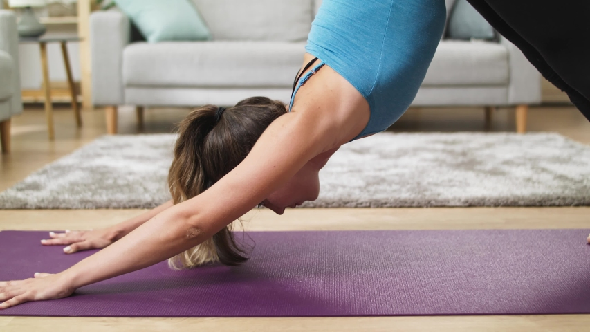 Close up shot of Woman does yoga poses dog in the morning in cozy living room | Shutterstock HD Video #1036257719