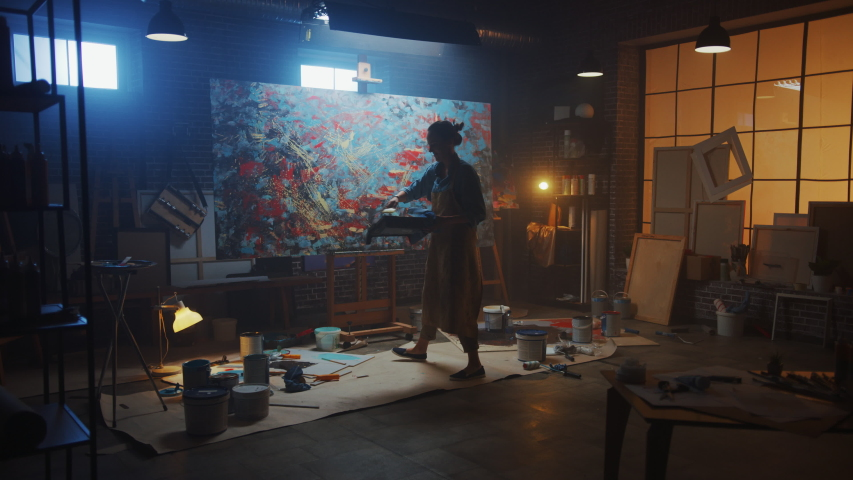 Talented Female Artist Working on a Modern Abstract Oil Painting, Uses Splattering and Dripping with Paint Brush Technique. Dark Creative Studio Large Picture Stands on Easel Illuminated. Slow Motion #1036269938
