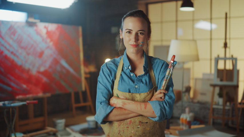 Portrait of Talented Young Female Artist Dirty with Paint, Wearing Apron, Crosses Arms while Holding Brushes, Looks at the Camera with a Smile. Authentic Creative Studio with Large Canvas and Tools  #1036269968
