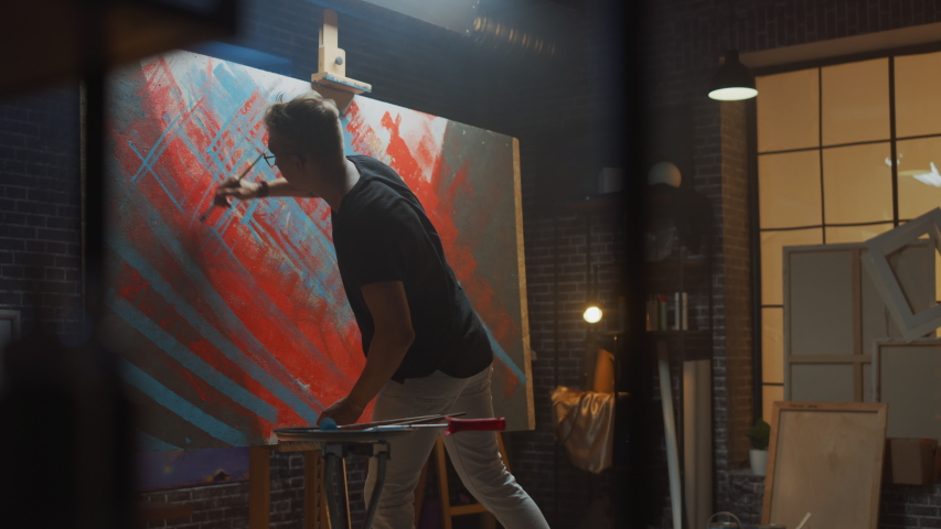 Talented male Artist Works on Abstract Oil Painting, with Broad Strokes of Paint Brush he Creates Modern Masterpiece. Dark and Messy Creative Studio where Large Canvas Stands on Easel Illuminated | Shutterstock HD Video #1036269983