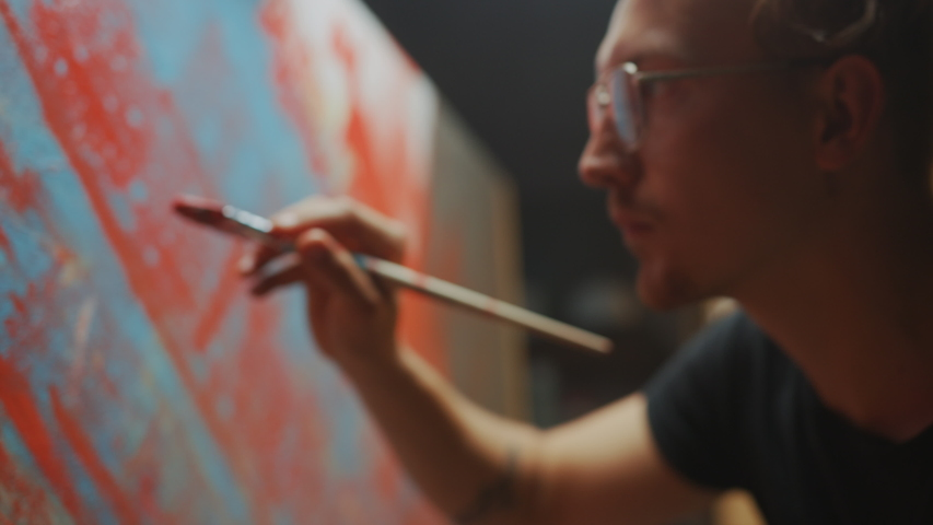 Portrait of Talented Artist Working on Abstract Painting, Uses Paint Brush To Create Daringly Emotional Modern Picture. Dark Creative Studio Large Canvas Stands on Easel. Side View Closeup Arc Shot
