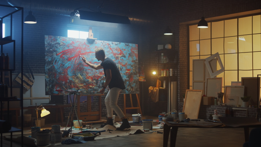 Talented Male Artist Energetically and Violently Using Paint Brush he Creates Modern Masterpiece of the Oil Painting. Dark and Messy Creative Studio with Large Canvas of Striking Colors | Shutterstock HD Video #1036270034