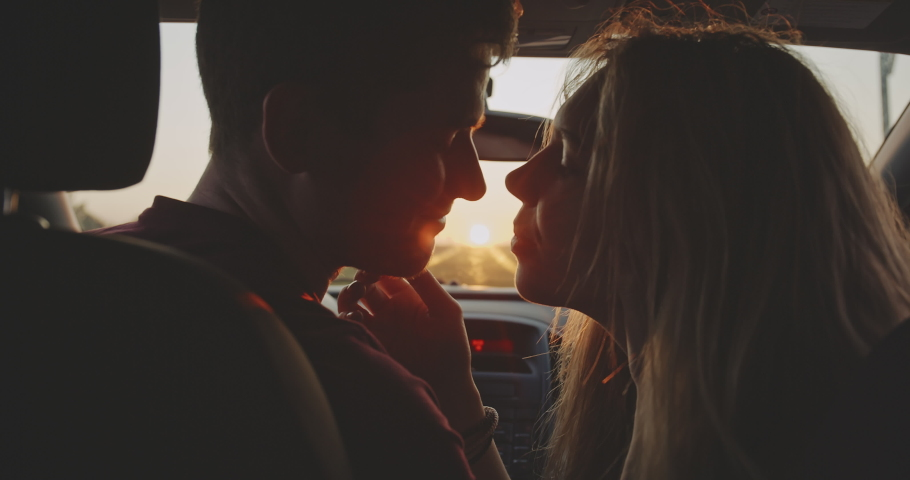Romantic young couple kiss on the front sit of their car during the road trip. Beautiful young woman kissing her boyfriend at sunset golden light at first date. Concept of love, relations and travel.