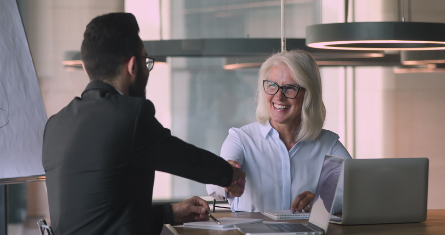 Happy middle aged mature caucasian businesswoman and young arabic arab businessman talking negotiating handshaking at office business meeting make commercial partnership agreement deal concept Royalty-Free Stock Footage #1036280456