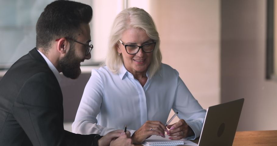 Old middle aged female professional bank manager investment advisor consulting commercial customer arabic eastern businessman explaining online project offer on laptop computer at business meeting Royalty-Free Stock Footage #1036280462