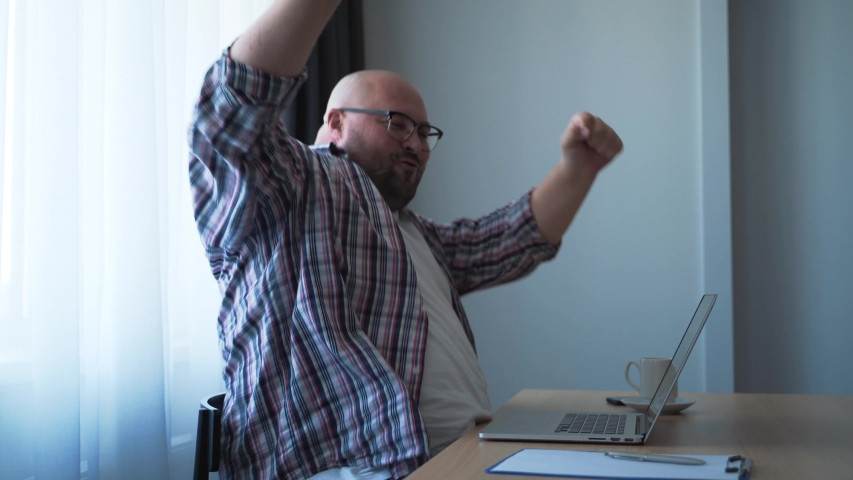 Happy funny fat bald man in glasses rejoices and emotionally expressively dances while sitting at table in office in front of laptop | Shutterstock HD Video #1036284227
