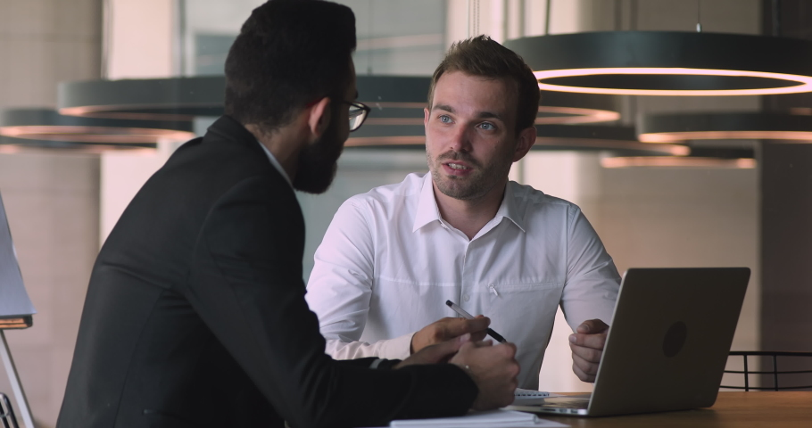 Confident male caucasian financial consultant adviser expert talking to arab client customer explain commercial investment deal benefit show computer presentation at bank loan negotiation meeting | Shutterstock HD Video #1036284896