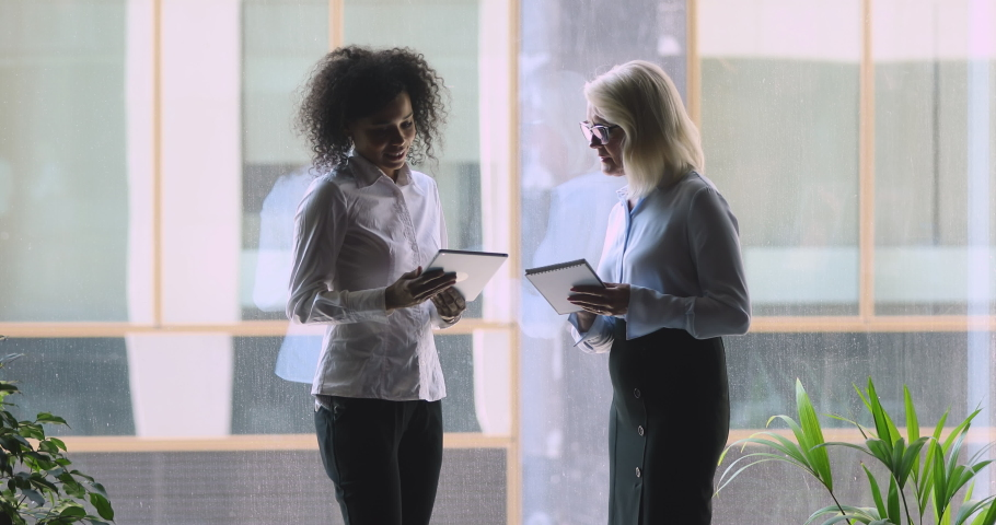 Happy mature caucasian company leader boss check work plan on notepad and digital tablet handshake african young female employee business partner make agreement shake hands stand at office window Royalty-Free Stock Footage #1036285055