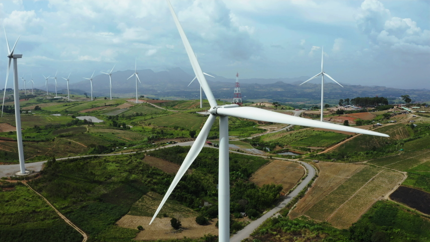 Aerial view, windmills rotating by the force of the wind and generating clean renewable energy for sustainable development in a green ecologic way on cloudy sky at highland. The look up shot by drone | Shutterstock HD Video #1036297355