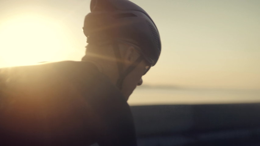 Triathlete Training On Bike.Cycling Exercise On Bike.Cyclist Rider In Helmet And Sportswear Riding Workout At Sunset On Triathlon Time Trial Bicycle.Cyclist Professional Fit Man On Triathlon Bicycle. | Shutterstock HD Video #1036307813