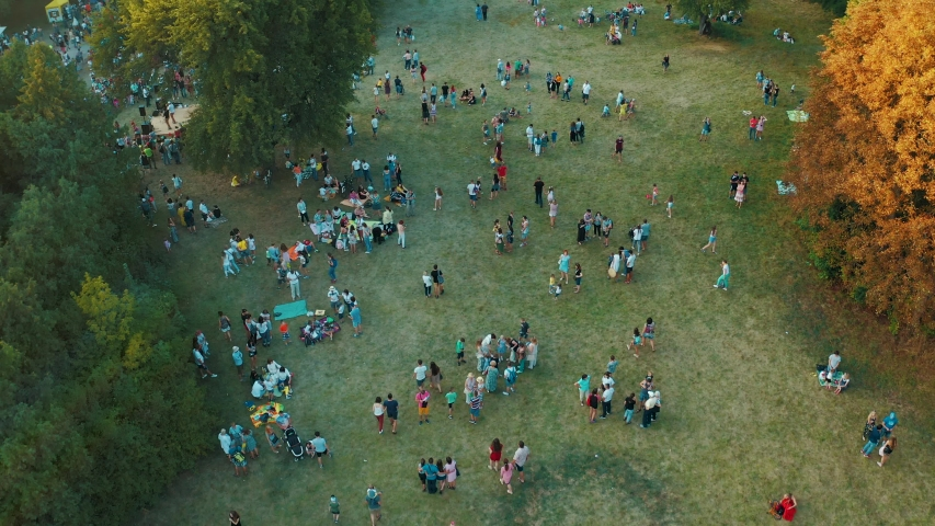 Crowd of people are walking, playing and having a picnic outdoors at summer. People having their carefree time in public park. Aerial view from above 4k