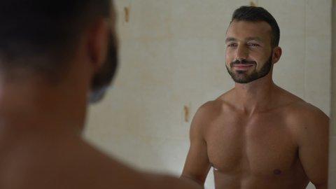 Macho man applying antiperspirant to armpit, preparing to workout in gym