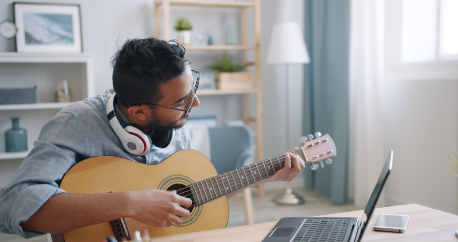 Young Arab guitarist is playing the guitar and using laptop typing at home alone enjoying leisure time in apartment. Hobby, music and youth concept. | Shutterstock HD Video #1036319162