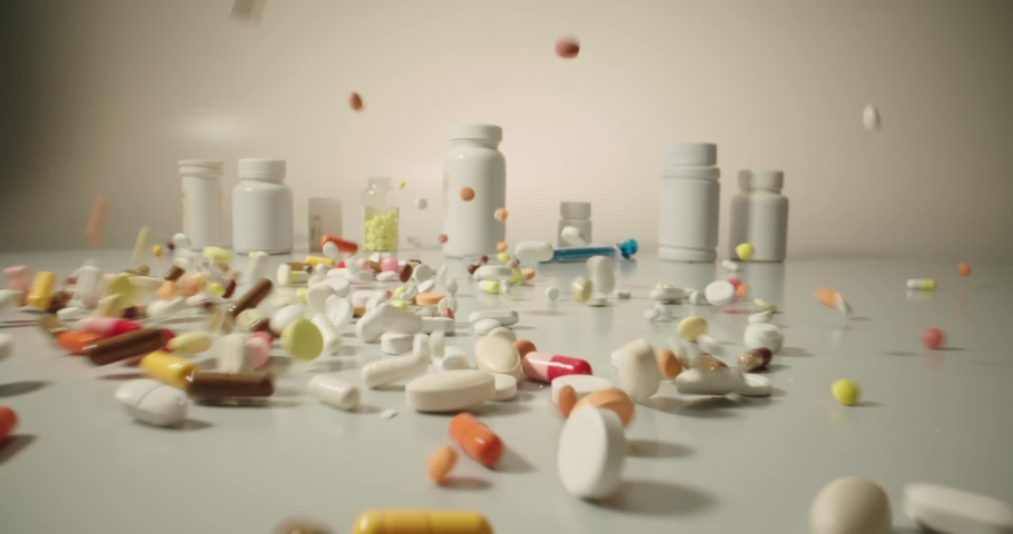 Closeup shot of different pills falling on table with tablets cans and syringes - mosern drug and pharmacy addiction, pharmaceutical industry concept 4k footage