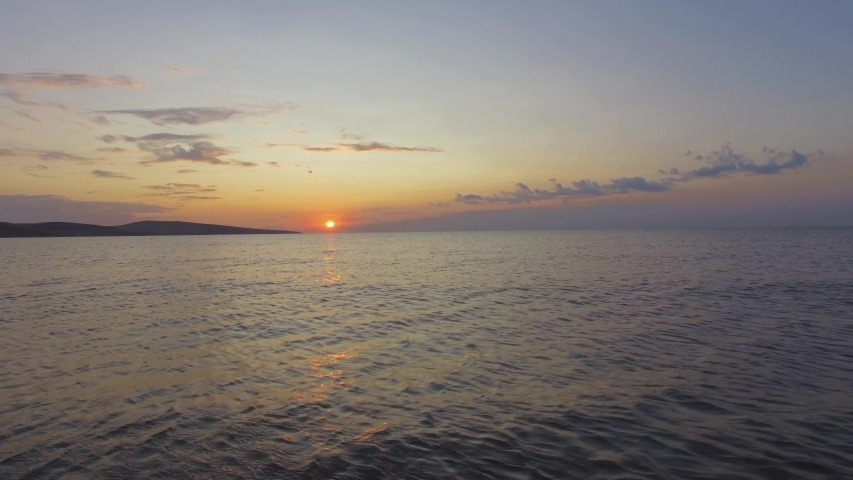 AERIAL: Sea surface with reflections of sunrise. Golden reflections on sea water surface at sunrise, aerial video, drone point of view, drone flying above the sea surface, close up | Shutterstock HD Video #1036327592