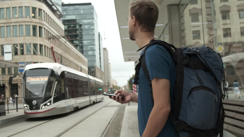 Millennial man tourist with backpack and smartphone stand on public transport stop and waiting tram in modern city center. Travel concept. Royalty-Free Stock Footage #1036327883