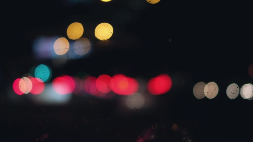 Beautiful glittering bokeh in dark blurry background at night. The round colorful bokeh shine from car lights in traffic jam on city street. It reflect lonely capital city lifestyle. Abstract concept.