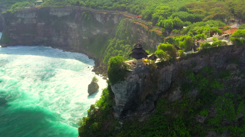 Pura Uluwatu temple. Stone cliffs, ocean waves and oceanscape. Aerial top view. Bali, Indonesia. Royalty-Free Stock Footage #1036331222