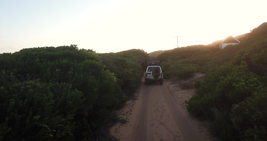 Off-road vehicle driving in a countryroad at sunset Royalty-Free Stock Footage #1036335608