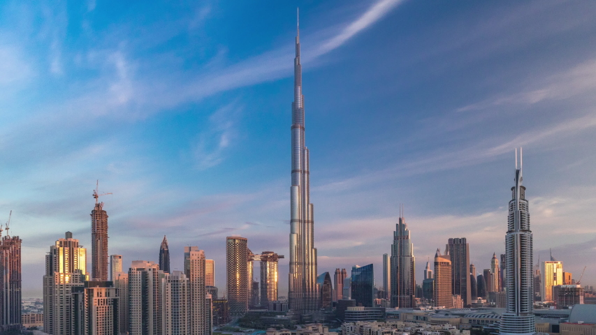 Dubai Downtown skyline timelapse with towers with long shadows during sunrise paniramic view from the top in Dubai, United Arab Emirates. Traffic on circle road and old style buildings
