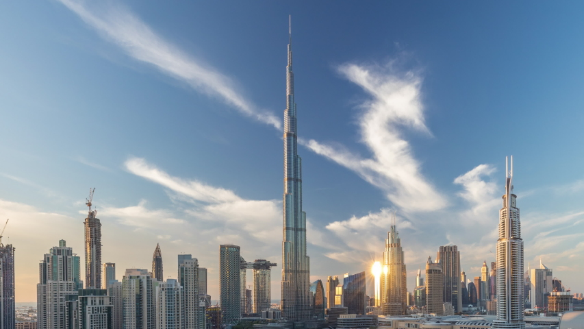 Dubai Downtown skyline day to night transition timelapse with towers paniramic view from the top in Dubai, United Arab Emirates. Traditional and modern buildings. Traffic on circle road and fountains