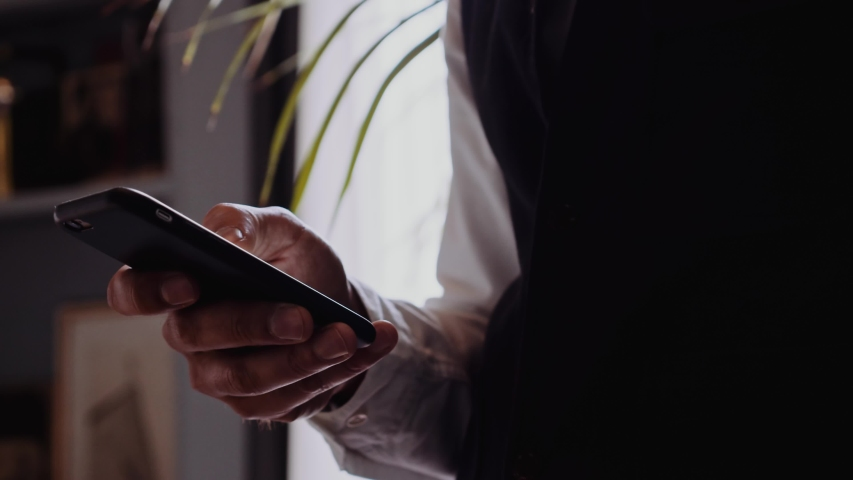 Businessman checking mobile phone standing in the office Royalty-Free Stock Footage #1036342928