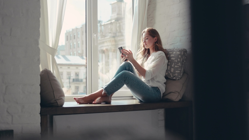 Charming young woman sitting on a windowsill at home and texting on her phone communication female looking message cellphone cheerful smile use internet modern smartphone portrait slow motion Royalty-Free Stock Footage #1036344536