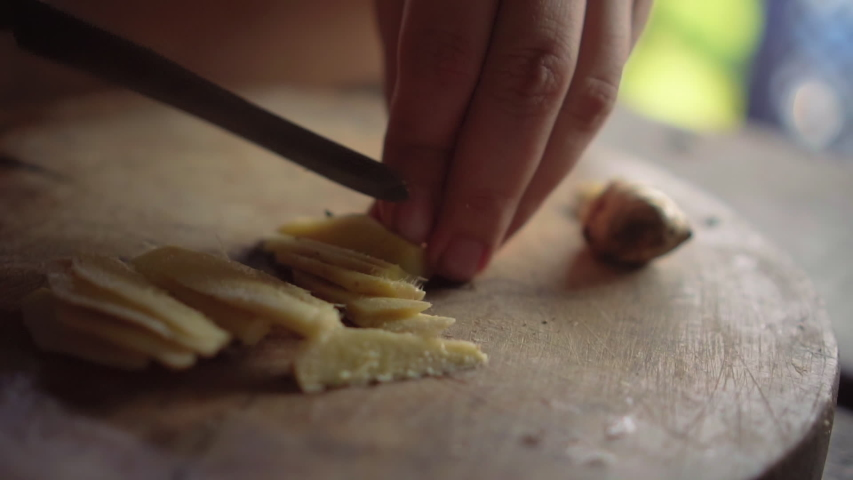Lady chopping ginger to pieces on wooden board. Slow motion.   Shutterstock HD Video #1036345082