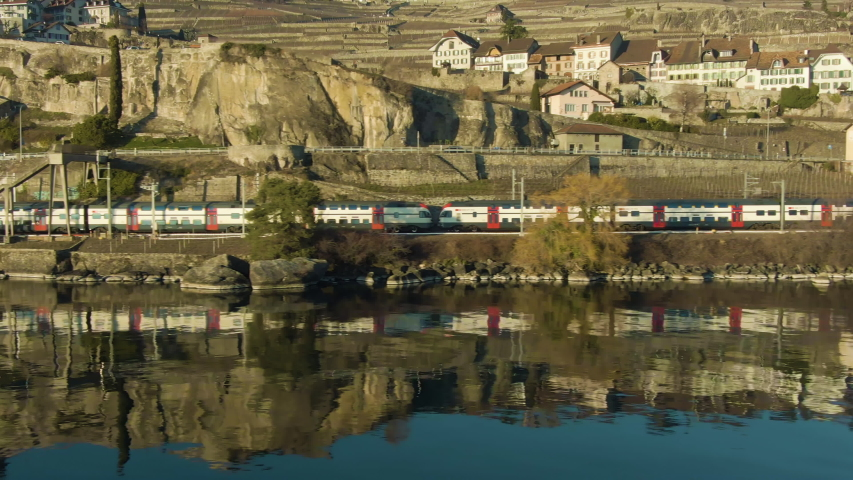 Double-Decker Passenger Train Goes Along Lake Geneva Shore. Reflection in Water. Terraced Vineyards of Lavaux and Village. Switzerland. Aerial Low-Level Shot. Drone Flies Sideways