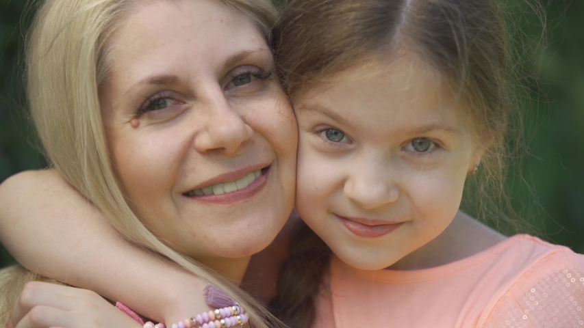 Close-up portrait smiling blond mother and her little daughter hugging in the summer park looking at camera. Happy loving family. Woman and girl together outdoors. | Shutterstock HD Video #1036348508