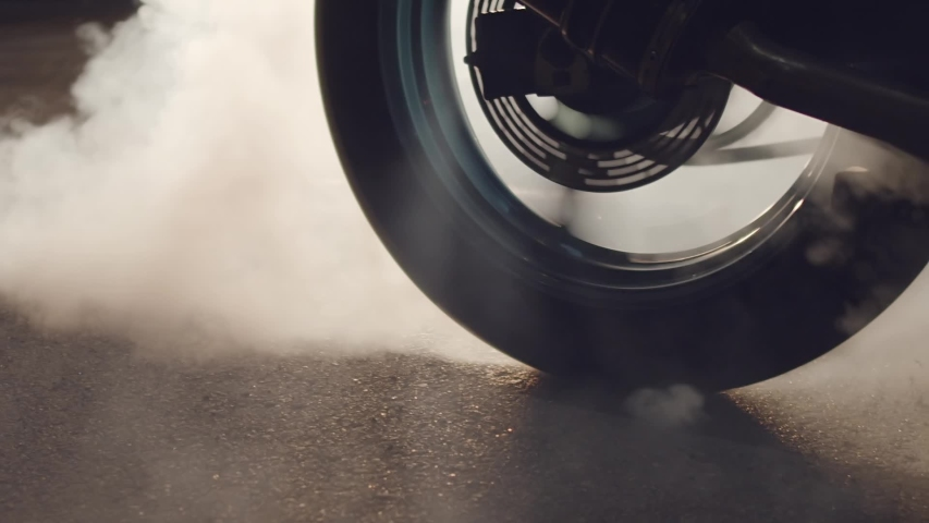 Close up of a motorcycle wheel burning rubber. Smoke and sparks from under the wheels of a sport motobike. Night racing. Need for speed. | Shutterstock HD Video #1036350872