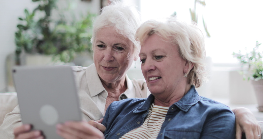 Mature lesbian couple looking at digital tablet together on sofa | Shutterstock HD Video #1036351412