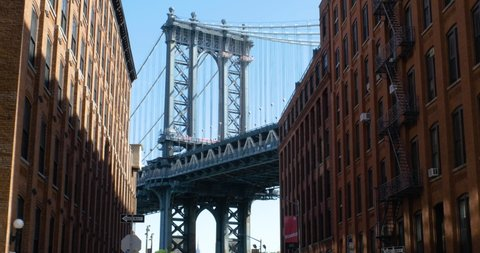 Wide shot looking at Manhattan bridge down street with brick buildings on sides.