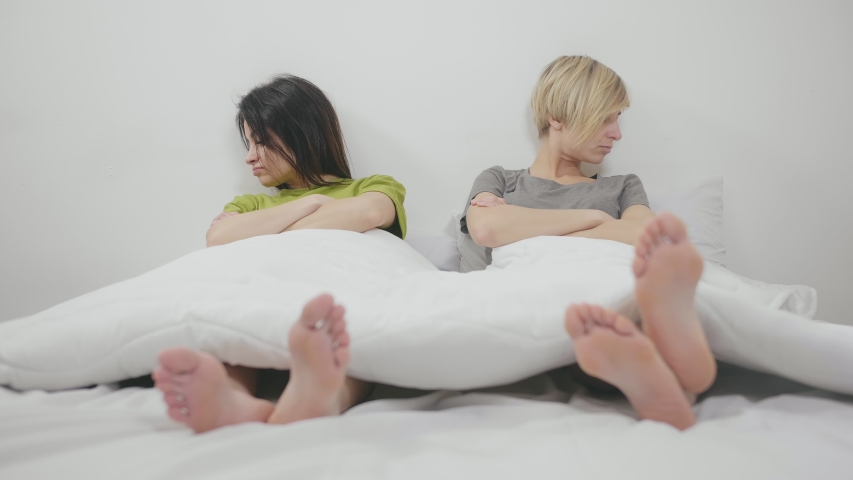 Portrait of lesbian couple lying in bed after fight and argument, ignoring and not looking at each other | Shutterstock HD Video #1036423772