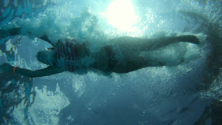 Girl plunging in water, shot from below. Slow motion shot at 100 fps Royalty-Free Stock Footage #1036429856